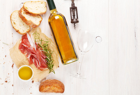 Prosciutto, wine, ciabatta, parmesan and olive oil on wooden table. Top view with copy space Фото со стока
