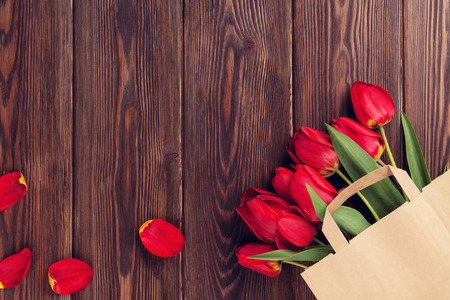 Red tulips bouquet in paper bag over wooden table background with copy space photo