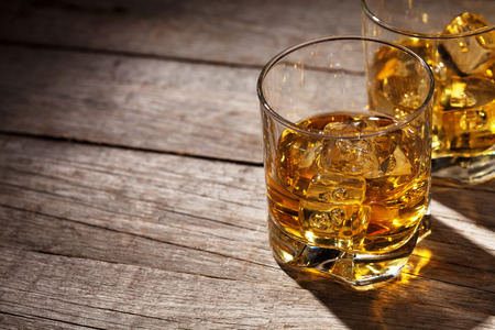 table glass: Glasses of whiskey with ice on wooden table with copy space