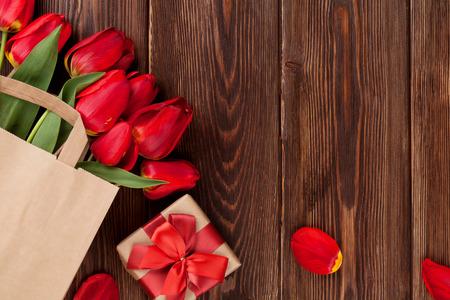 mazzo di fiori: Tulipani rossi bouquet nel sacchetto di carta e confezioni regalo su sfondo tavolo in legno con spazio di copia