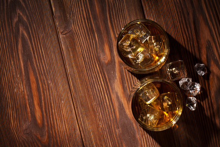 Glasses of whiskey with ice on wooden table. Top view with copy space