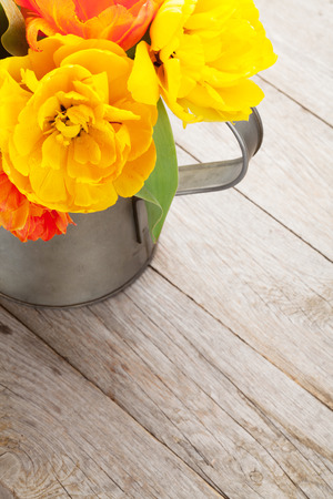 Colorful tulips bouquet in watering can on wooden table photo