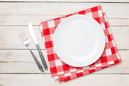 Empty plate, silverware and towel over wooden table background. View from above with copy space Archivio Fotografico