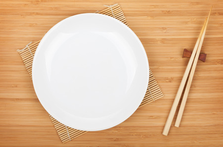 Empty plate and sushi chopsticks on bamboo table