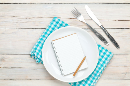 recipe background: Notepad for recipe over empty plate and silverware on white wooden table background