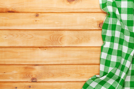 picnic cloth: Green towel over wooden kitchen table. View from above with copy space