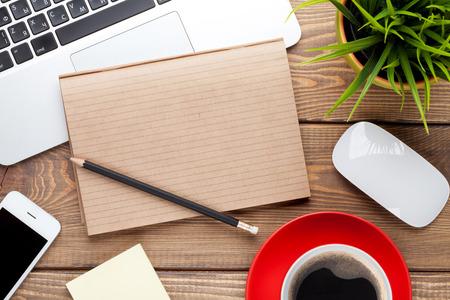 Mesa escritorio de oficina con el ordenador, los suministros, la taza de café y flor. Vista superior con espacio de copia