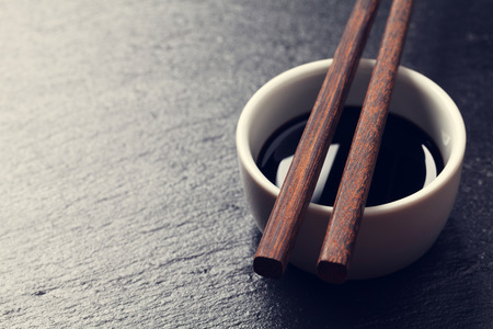 sauce bowl: Japanese sushi chopsticks over soy sauce bowl on black stone background. Top view with copy space. Toned Stock Photo