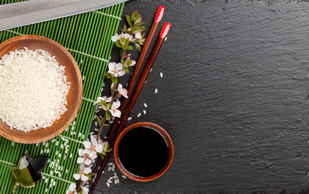 sushi restaurant: Japanese sushi chopsticks, soy sauce bowl, rice and sakura blossom on black stone background. Top view with copy space