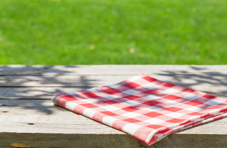 tablecloth: Empty wooden garden table with tablecloth with green bokeh background