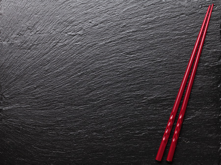 Japanese sushi chopsticks on black stone background. Top view with copy space