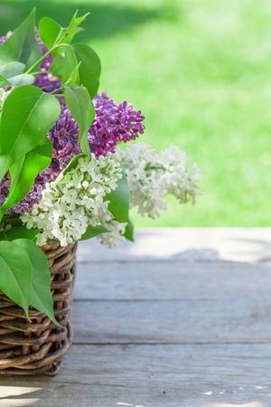 Colorful lilac flowers in basket on garden table photo