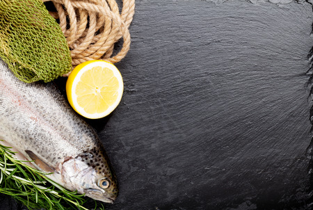 rainbow fish: Fresh raw rainbow trout fish with spices on black stone with copy space Stock Photo