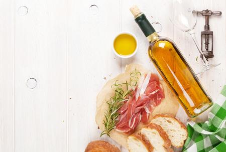 pan y vino: Prosciutto, el vino, ciabatta, parmesano y aceite de oliva en la mesa de madera. Vista superior con espacio de copia Foto de archivo