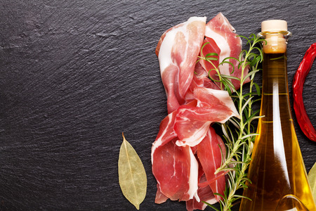 Prosciutto with rosemary and olive oil on stone table. Top view with copy space Stock Photo