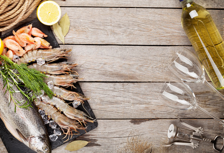 Fresh raw sea food with spices and white wine on wooden table background. Top view with copy space Imagens