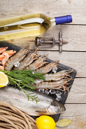 food and wine: Fresh raw sea food with spices and white wine on wooden table background. Top view