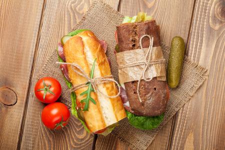 サラダ、ハム、チーズ、トマトに木製のテーブルと 2 つのサンドイッチ。トップ ビュー