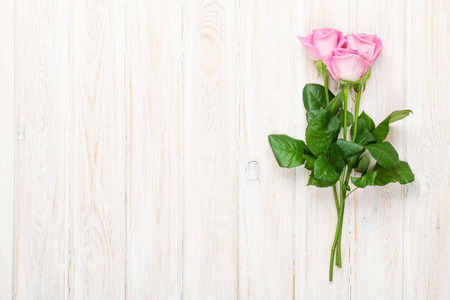 Pink roses bouquet over white wooden table. Top view with copy space Stock Photo