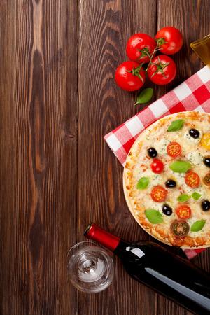 vin chaud: Pizza italienne avec du fromage, les tomates, les olives, le basilic et le vin rouge sur la table en bois. Vue de dessus avec copie espace