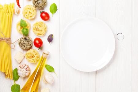 Italian food cooking ingredients and empty plate. Pasta, tomatoes, basil. Top view with copy space photo