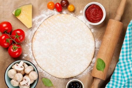 masa: Ingredientes para cocinar la pizza. Masa, verduras y especias. Vista superior con espacio de copia