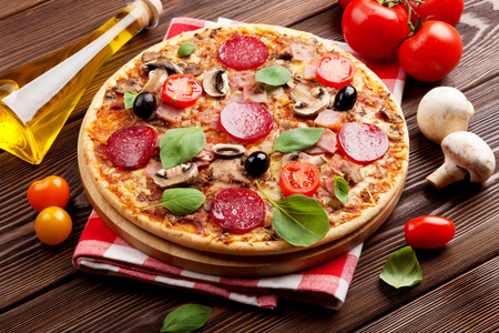 Italian pizza with pepperoni, tomatoes, olives and basil on wooden table Standard-Bild