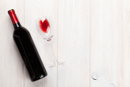 still life of wine: Red wine glass and bottle over white wooden table with copy space
