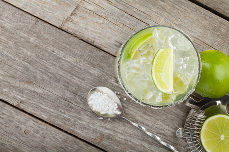 margarita cóctel: Cóctel clásico margarita con borde salado en mesa de madera con limas y utensilios de bebidas