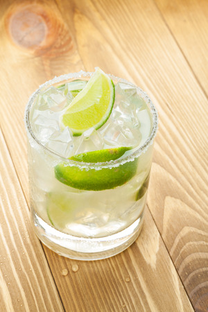 margaritas: Classic margarita cocktail with salty rim on wooden table