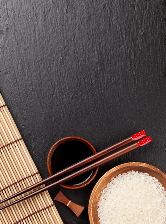sauce bowl: Japanese sushi chopsticks over soy sauce bowl and rice on black stone background. Top view with copy space