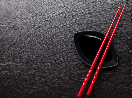 Japanese sushi chopsticks over soy sauce bowl on black stone background. Top view with copy space photo