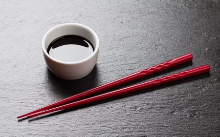 sushi menu: Japanese sushi chopsticks and soy sauce bowl on black stone background. Top view with copy space