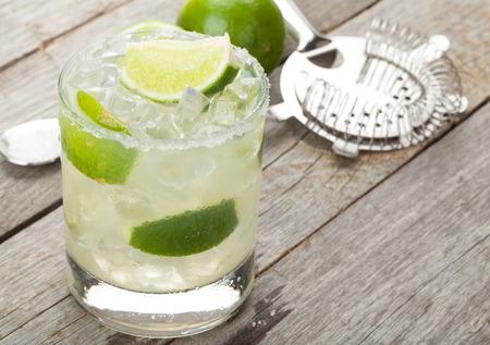 alimentos y bebidas: Cóctel clásico margarita con borde salado en mesa de madera con limas y utensilios de bebidas