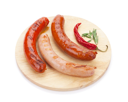 Various grilled sausages with spices on cutting board. Isolated on white background photo