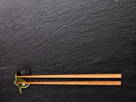 黒い石の背景に日本の寿司箸。コピー スペース平面図 写真素材