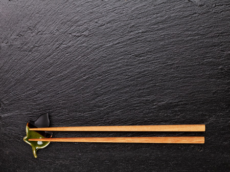 sushi chopsticks: Japanese sushi chopsticks on black stone background. Top view with copy space