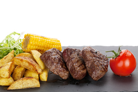 grilled potato: Steak with grilled potato, corn, salad and tomato. Isolated on white background