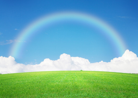 Green grass field, blue sky with clouds on horizon and rainbow background photo