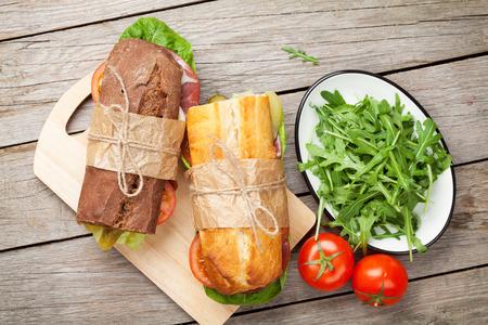 jamon y queso: Dos emparedados con ensalada, jamón, queso y tomates en la tabla de cortar
