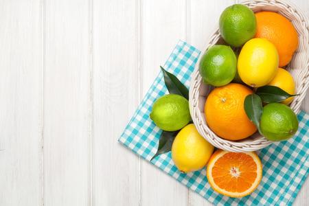 Citrusvruchten in de mand. Sinaasappels, limoenen en citroenen Over witte houten tafel achtergrond met een kopie ruimte Stockfoto