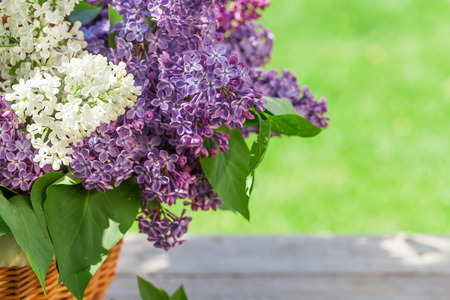 Colorful lilac flowers in basket on garden table with copy space photo