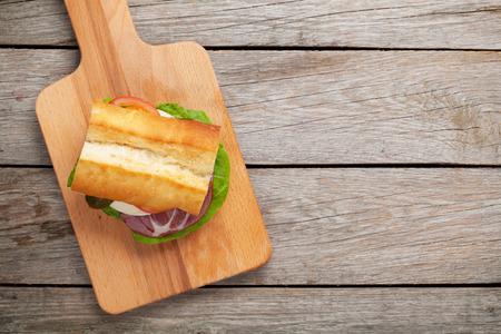 Sandwich con ensalada, jamón, queso y tomates en la tabla de cortar. Vista superior con espacio de copia Foto de archivo - 40775518