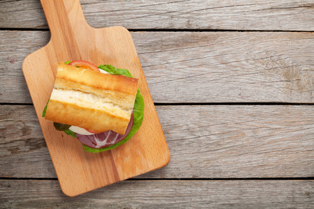 sliced cheese: Sandwich with salad, ham, cheese and tomatoes on cutting board. Top view with copy space Stock Photo