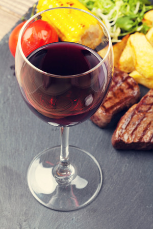 Red wine glass and steak with grilled potato, corn, salad on stone plate photo