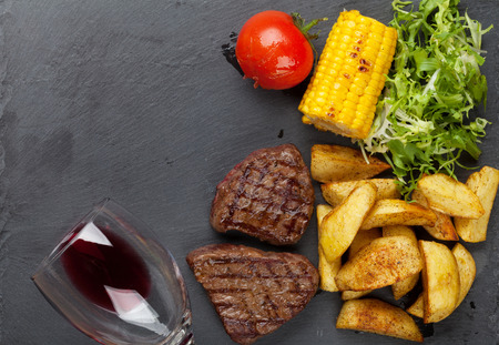 grilled potato: Beef steak with grilled potato, corn, salad and red wine. Top view with copy space Stock Photo