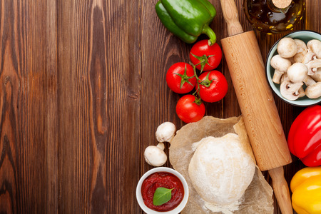 Pizza cooking ingredients. Dough, vegetables and spices. Top view with copy space Banco de Imagens