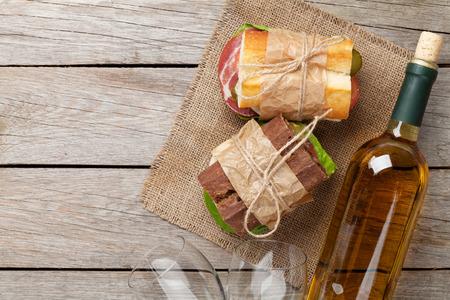 bocadillo: Dos bocadillos y vino blanco en mesa de madera. Vista superior con espacio de copia Foto de archivo