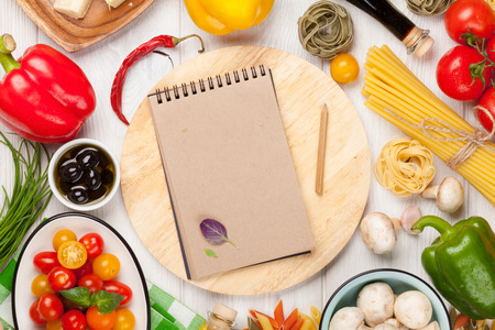 Italian food cooking ingredients. Pasta, vegetables, spices. Top view with notepad for copy space Stock Photo
