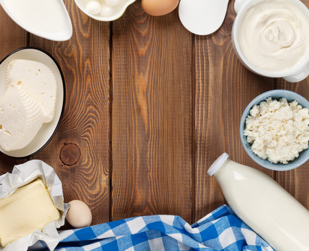 Dairy products on wooden table. Sour cream, milk, cheese, eggs, yogurt and butter, Top view with copy space photo